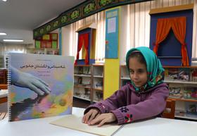 دستهای کودکان نابینا کتابهای بریل کانون را لمس میکند